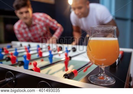 Selective Focus On A Beer Glass, Two Male Friends Playing Table Foosball On The Background, Copy Spa
