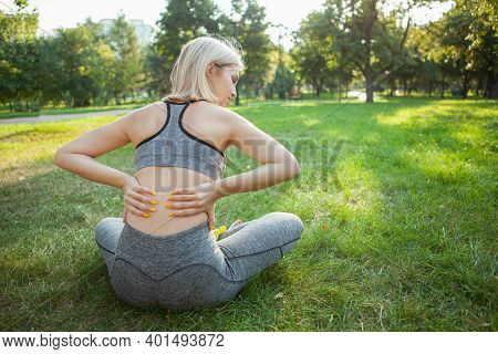 Rear View Shot Of A Sportswoman Sitting On The Grass, Rubbing Her Back. Female Athlete Suffering Fro