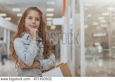 Beautiful Little Curly Haired Girl Enjoying Shopping At The Mall. Lovely Little Shopper Examining Sh
