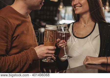 Selective Focus On Glasses Of Beer Clinking In The Hands Of Couple Celebrating Anniversary At Restau