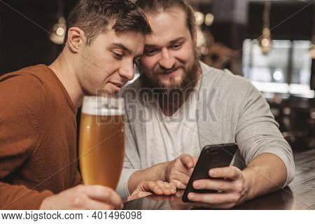Two Male Friends Enjoying Resting At Beer Pub Together, Checking Out News Online, Using Smart Phone.