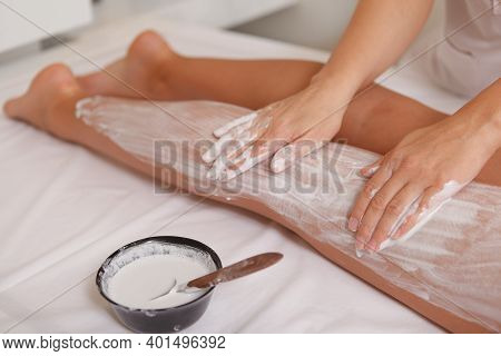 Top View Cropped Shot Of Spa Therapist Applying Body Mask On The Legs Of A Female Client. Woman Gett