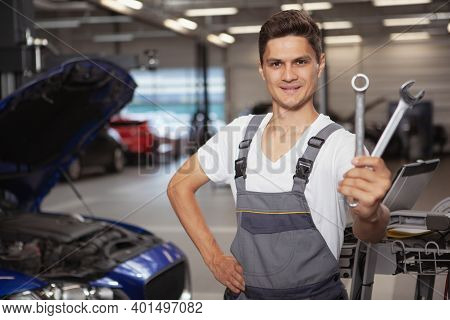 Happy Handsome Young Car Mechanis Smiling, Holding Out His Repair Tools To The Camera. Cheerful Auto