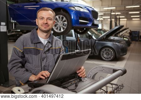 Cheerful Mature Male Car Mechanic Smiling To The Camera, Working On A Computer At His Garage. Happy