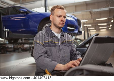 Mature Male Car Mechanic Looking Concentrated, Doing Computer Diagnostics On A Broken Automobile At