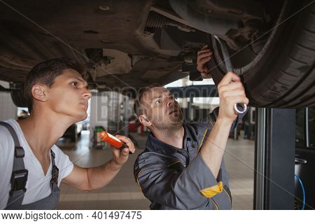 Two Car Mechanics Working Underneath A Broken Vehicle At The Garage. Experienced Auto Technicians Ma