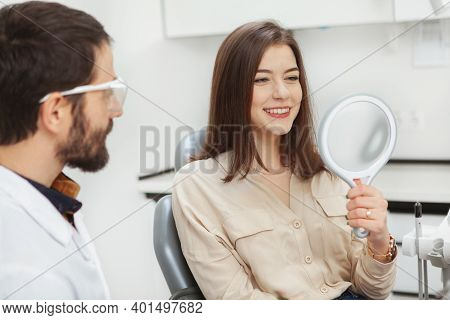 Attractive Young Woman Checking Her Teeth In The Mirror After Dental Treatment At The Clinic. Health