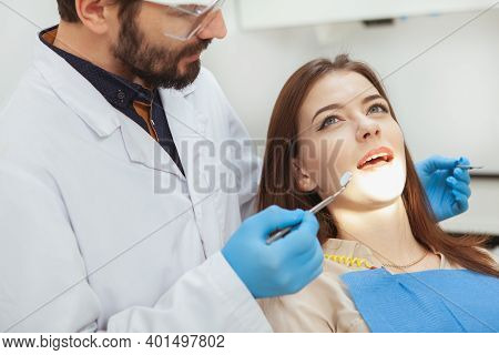 Yong Woman Having Her Teeth Examined By Experienced Dentist. Cropped Shot Of A Male Dentist Checking