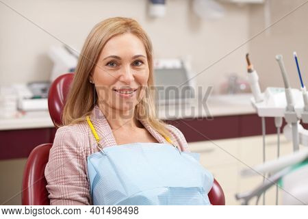 Senior Lady Sitting In A Dental Chair At The Clinic, Waiting For Medical Appointment With Her Dentis