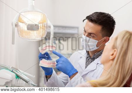 Male Dentist Explaining His Female Patient About Teeth Care, Showing Her Dental Mold. Professional D