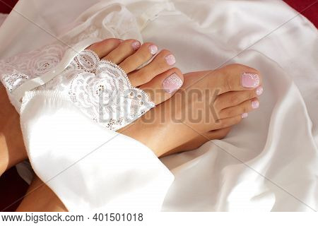 Beautiful Bare Legs Of The Bride Under Veil Lying On The Bed. High Quality Photo