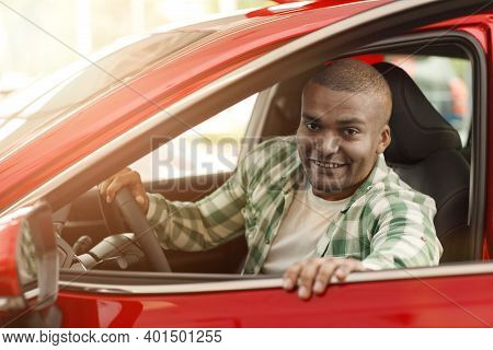 Happy African Man Smiling To The Camera While Getting In A New Car At The Dealership. Cheerful Male