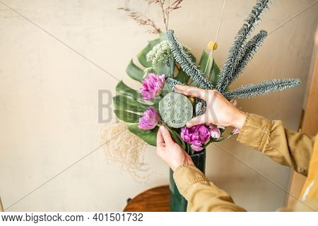 Female Making A Composition Of Fresh Flowers On A Beige Wall Background. Bouquet Of Nobilis, Monster