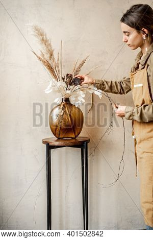 Woman Decorating Home With A Composition Of Dried Flowers And Herbs In A Glass Vase On A Beige Wall