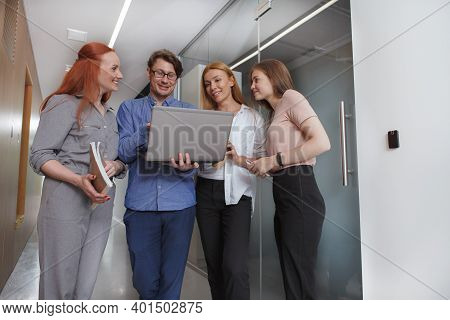 Low Angle Shot Of Group Of Business People Using Laptop On The Go, Walking In The Corridor