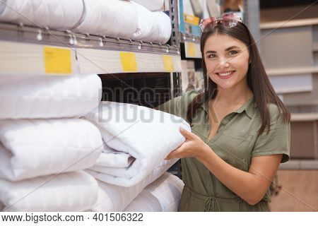Young Woman Buying New Blanket At Furnishings Store