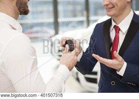 Cropped Dshot Of A Cheerful Salesman Giving Car Keys To A Man. Happy Owner Receiving Car Key To Hi N
