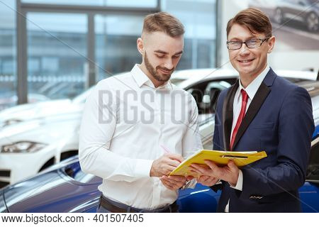 Mature Salesman Smiling To The Camera While His Client Signing Papers On Car Sale. Young Man Closing