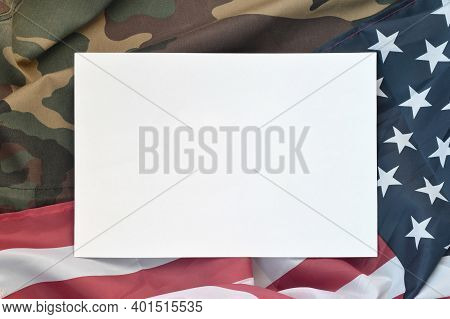 Blank Paper Lies On United States Of America Flag And Folded Military Uniform Jacket. Military Symbo