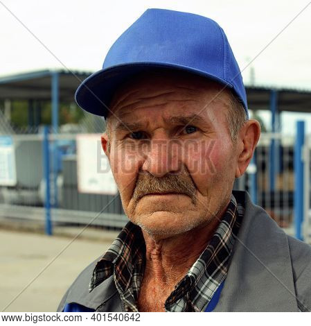 A Tired And Sad Old Man In A Baseball Cap With Copy Space Looks At The Camera. Portrait Of An Old An