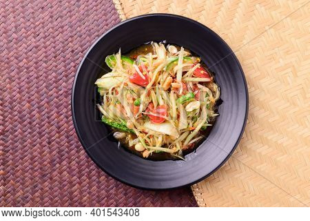 Thai Food (som Tum), Spicy Green Papaya Salad On Woven Bamboo Background, Top View