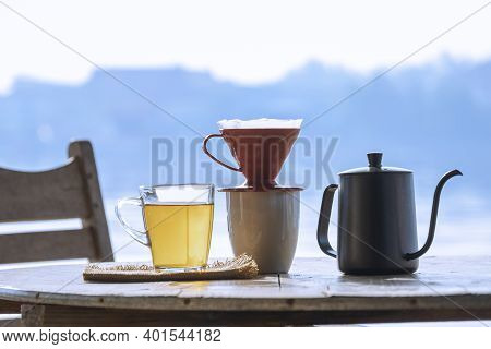 Glass Cup Of Hot Aromatic Tea With Drip Coffee Cup Set On Wooden Round Table Against Riverside View