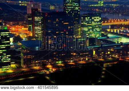 Vienna Modern District In The Night . Aerial View Of Illuminated Capital City In The Nighttime . Sky