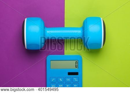 Fitness, Weight Loss Still Life. Calorie Counting. Calculator And Dumbbell On Green Purple Backgroun