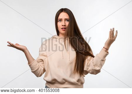 Studio Shot Of Insecure Puzzled Young Female With Long Chestnut Hair, Spreads Hands With Doubt, Wear