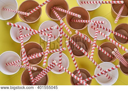 Drinking Red Tubes Straws Made Of Paper And Cornstarch In Empty Paper Coffee Cups On A Trendy Yellow