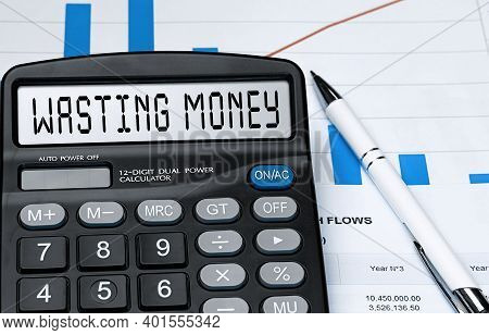 Calculator With The Word Wasting Money On The Display. Money, Finance And Business Concept