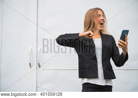 Outdoor Portrait Of Ecstatic Modern Businesswoman Who Is Joyful. She Is Holding Smartphone.