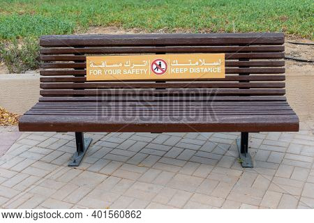 Abu Dhabi, Uae - July 17, 2020: Empty Wooden Bench In The Public Park In Abu Dhabi With Sign For You