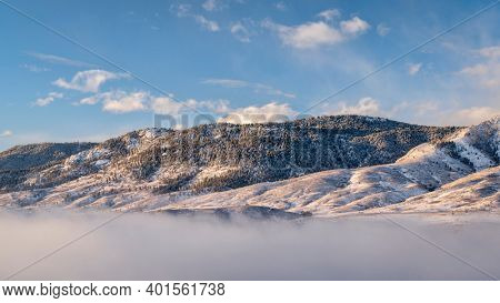 morning fog over mountain lake at foothills of Rocky Mountains - Horsetooth Reservoir in northern Colorado, winter scenery with fresh snow