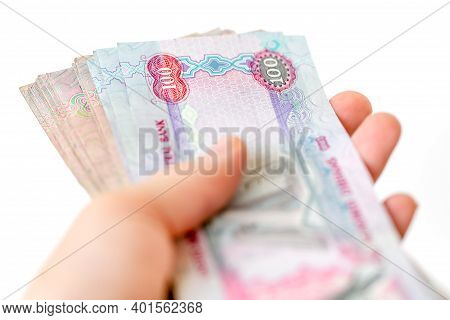 Stack Of Uae Dirhams In Woman's Hands Isolated On White Background. Closeup.