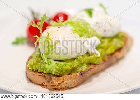 Avocado Toast With Poached Eggs And Grilled Tomatoes, Closeup