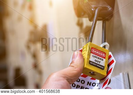 Hand Holding Yellow Key Lock And Tag For Process Cut Off Electrical,the Toggle Tags Number For Elect