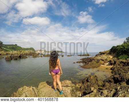White Caucasian Brunette Woman, With A Nice Ass In A Bikini Facing The Sea. Crystal Clear Water, Can
