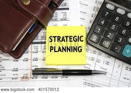 Strategic Planning Is Written On A Yellow Sheet That Lies On The Document Among The Notepad And Calc