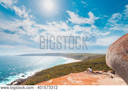 Woman Sitting On The Edge Of The Cliff At Remarkable Rocks On Kangaroo Island, South Australia