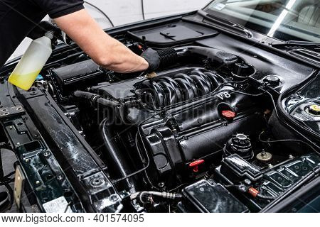 Car Wash Worker Carefully Cleaning Car Engine