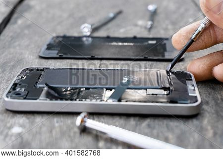 The Technician Holding A Screwdriver A Mobile Phone Repair Closeup Inside Cell Phone With A Fixing B