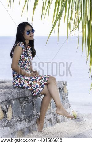 Young Attractive Girl In A Dress Sitting On A Stone Wall