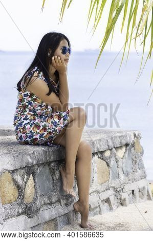 Indonesian Girl With Sunglasses In A Dress Sitting On A Stone Wall