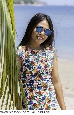 Indonesian Girl With Sunglasses Standing Near A Palm Leaf