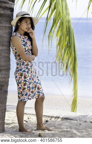 Young Attractive Girl With A Hat Standing Near A Palm Tree