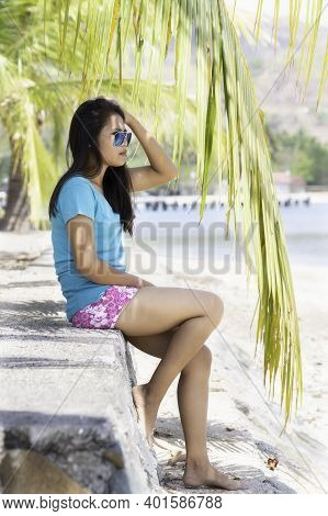 Indonesian Girl With Sunglasses Sitting In Shorts On A Stone Wall