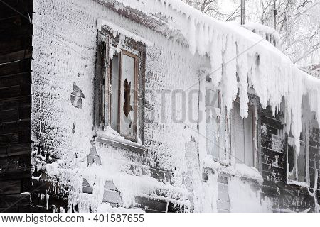 Frozen And Broken Windows Of An Old Wooden Residential Building Close Up