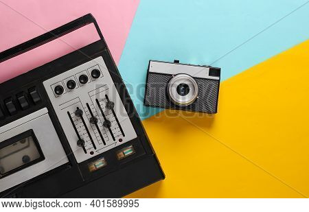 Retro Audio Tape Recorder And Film Camera. Retro Media On Colored Background. Top View. 80s