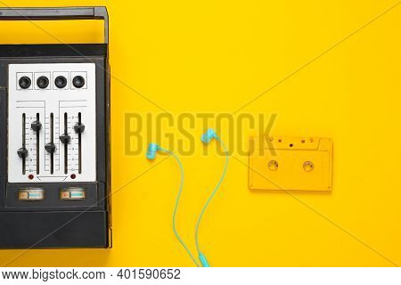 Retro Audio Tape Recorder, Earphones And Audio Cassette. Retro Media On Yellow Background. Top View.